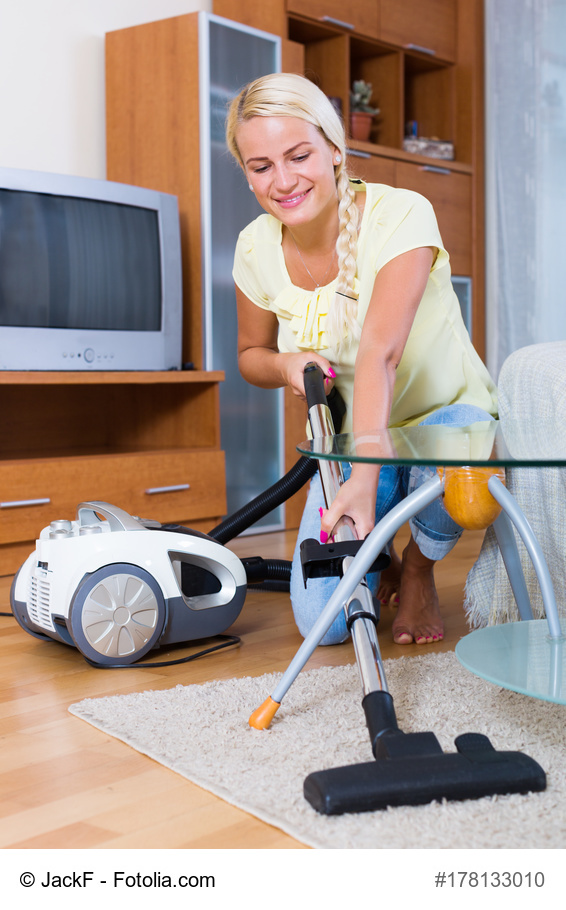 smiling woman using vacuum cleaner during regular clean-up